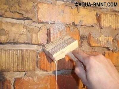 Рабочий грунтует стену печи