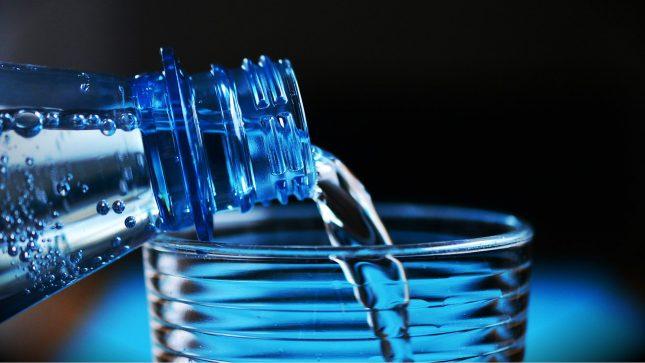 Наливают воду из бутылки в стакан